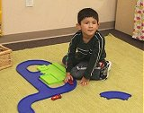 Child playing with cars and track equipment